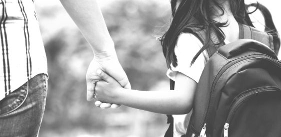 parent holding hands with child wearing backpack